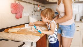 Portrait of young beautiful woman teaching her little child boy making cookies and baking pies on kitchen at home. Portrait of young beautiful women teaching stock photography