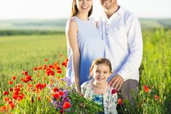 Portrait of a young big pregnant family in poppy field Stock Photo