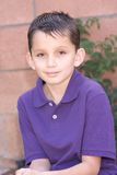 Portrait young biracial boy by brick wall Stock Image