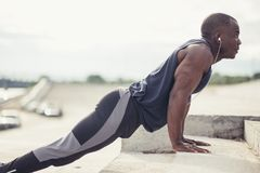 Young athletic man doing push-ups. Fitness model doing outdoor workout. stock photo