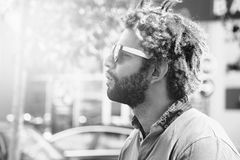 Portrait of young black man with dread locks. Wearing sunglasses. Black and white effect applied Royalty Free Stock Image