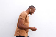 Young black man enjoying music on mobile phone against white background Stock Photos