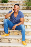 Young black man sitting on steps outside and talking on mobile phone Royalty Free Stock Images