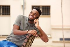 Young black man smiling and talking on mobile phone outside. Portrait of young black man smiling and talking on mobile phone outside Stock Photography