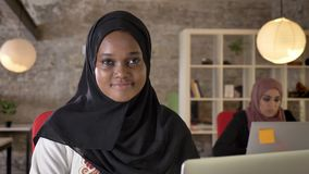 Portrait of young black muslim women in hijab working and smiling, looking into camera, two beautiful womens sitting in. Modern office stock video