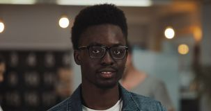 Portrait of young black smiling successful businessman wearing stylish glasses standing in modern office. Close up stock video footage