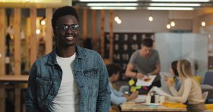 Portrait of young black smiling successful businessman wearing stylish glasses standing in modern office. Working people