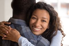 Portrait of young black smiling wife embracing husband. Portrait of black beautiful wife embracing husband. Close up african women looking at camera, men rear stock photos