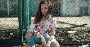 Portrait of a young black woman in urban background. Portrait of a young African American woman wearing bomber jacket posing over metal fence, outdoors Royalty Free Stock Photography
