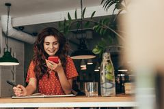 Portrait of young blogger using smartphone at table with notebook. In coffee shop royalty free stock photos
