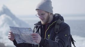 Portrait of young blond bearded handsome man in warm jacket and hat standing on the glacier checking with the map. Amazing nature of a snowy North or South stock video