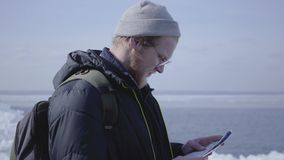 Portrait of young blond bearded handsome man wearing warm jacket and hat walking on the glacier checking with the map. Portrait of young blond bearded handsome stock video footage