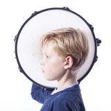 Portrait of young blond boy with drum against white background Royalty Free Stock Image