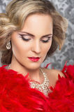 Portrait of a young blond bride in red feathers Stock Image