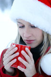 Portrait of a young blond girl drinking hot coffee. Portrait of a young and beautiful blond girl in a Christmas hat drinking hot coffee. The image is taken Royalty Free Stock Photos