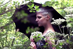 Portrait of a young blond girl with an umbrella in the meadow royalty free stock photography