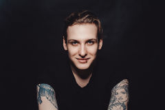 Portrait of a young blond guy with tattoos and piercings on a black background. Portrait of the young smiling man. another view Stock Photography