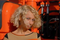 A portrait of a blond hair woman, standing near an orange crawler and looking playful with her blue eyes. A portrait of a young blond hair woman, standing near Royalty Free Stock Images