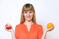 Portrait of young blond haired woman comparing apple to orange. On white background Royalty Free Stock Image