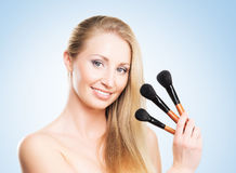 Portrait of a young blond holding makeup brushes Royalty Free Stock Image