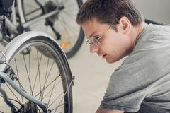 Portrait of a young blond man with short haircut in gray t-shirt with glasses sitting near wheel of broken bicycle. And looking sideways stock photos