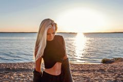 Portrait of a young blond sensual athletic fitness woman with a sunset on the background and sunlight in her hair royalty free stock images
