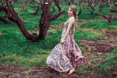 Portrait of a young blond woman on a background of flowering trees. girl spinning. pink dress fluttering in the wind Stock Photo