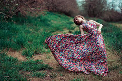 Portrait of a young blond woman on a background of spring trees. girl spinning. pink dress fluttering in the wind royalty free stock images