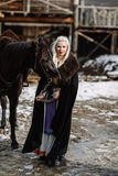 Portrait of a young blond woman in a black cloak with a horse. Stock Photos