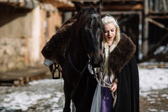 Portrait of a young blond woman in a black cloak with a horse. Royalty Free Stock Image