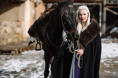 Portrait of a young blond woman in a black cloak with a horse. Noble Maidens Stock Image