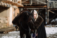 Portrait of a young blond woman in a black cloak with a horse. Royalty Free Stock Images