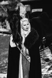 Portrait of a young blond woman in a black cloak with a horse. Stock Image
