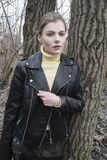 Portrait of a young blond woman in a black jacket in the woods. Portrait of the blonde girl in the woods Stock Photos