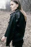 Portrait of a young blond woman in a black jacket in the woods. Portrait of the blonde girl in the woods Royalty Free Stock Images