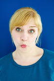 Portrait of young blond woman blowing a kiss Royalty Free Stock Photo