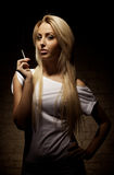 Portrait of young blond woman with a cigarette Stock Photos