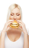 Portrait of a young blond woman eating a burger Stock Photos