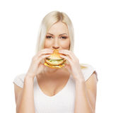 Portrait of a young blond woman eating a burger Royalty Free Stock Photography