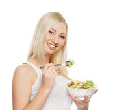 Portrait of a young blond woman eating a salad Royalty Free Stock Images
