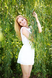 Portrait of a young blond woman in green willow tree Royalty Free Stock Photography