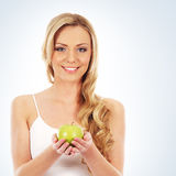 Portrait of a young blond woman holding an apple Stock Photos