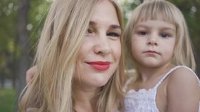 Portrait of young blond woman holding her cute daughter in white dress in arms looking at camera. Leisure outdoors. Portrait of young blond woman holding her stock video