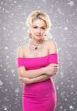 Portrait of a young blond woman in jewelry. Beautiful blond girl with luxury golden necklace over winter background. Christmas concept Royalty Free Stock Images