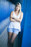 Portrait of young blond woman. Young blond woman posing on blue wall background Stock Photo
