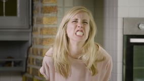 Portrait of a young blond woman roaring and showing her big teeth at the camera stock video footage