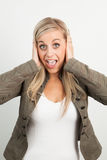 Portrait of a young blond woman smiling and doing a funny face Royalty Free Stock Photos