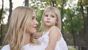 Portrait of young blond woman in white dress caressing her cute daughter. Leisure outdoors. Happy family. One parent. Motherhood, parenthood, happy childhood stock footage