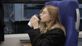 The portrait of young blond woman, who sits in the train, drinks coffee and using her smartphone. The blond lady in round stulish glasses has a red lipstic and stock video footage