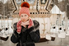Portrait of young blond woman in winter clothes. Red cap and mittens. Walking in the park royalty free stock photos